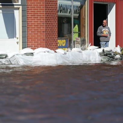 Kip Schoettmer, owner of John's Tire, looks out a doorway