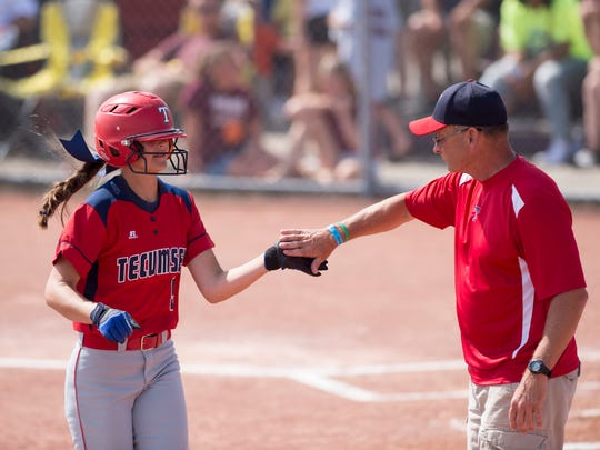 Tecumseh's Chloe Holder is congratulated by coach Gordon Wood after laying down a successful sacrifice bunt during their Class A state championship softball game at Ben Davis High School Saturday morning.