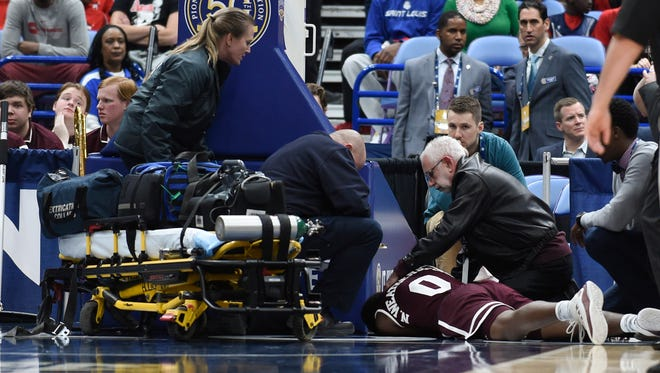 Nick Weatherspoon (0) is checked on by paramedics after sustaining an injury during the second half of the quarterfinals of the SEC Conference Tournament at Scottrade Center. Tennessee won 62-59.