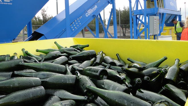 Green wine bottles are loaded into the SCSWA's industrial-sized glass crusher. Roll-off containers left at local festivals have increased the tonnage of glass collected.