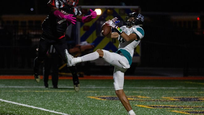 Tre Brown (11) catches a 26-yard pass for an Islands touchdown as Jenkins' Ronald Cooper (7) defends last year at Memorial Stadium.