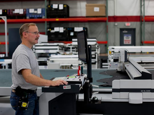 A worker uses a computer to cut leather for trim components Wednesday, November 11, 2015 at Eissmann Group Automotive, 2440 20th Street in Port Huron. Eissmann will be undergoing a two-phase expansion project, bringing the facility from 60,000-square-feet to 148,000-square-feet by 2018. The project is expected to increase employment from 108 to 160 jobs in 2016, with the possibility of more than 300 by 2018.