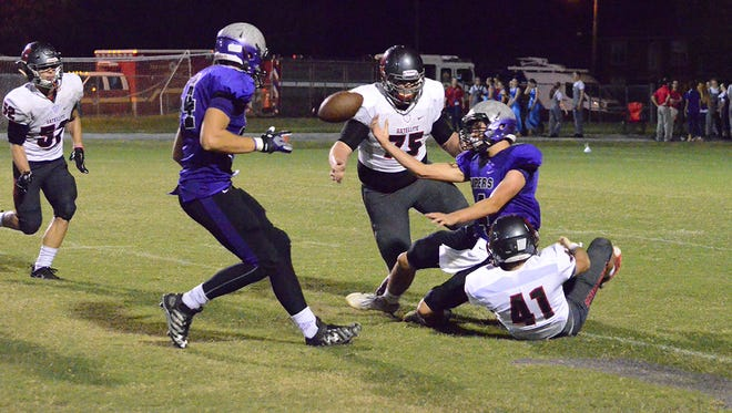 Quarterback Bradley Cantrell tries to get rid of the ball Friday night as defensive players Joe Schwarz (75) and Tanner Gamin (41) bring him down.