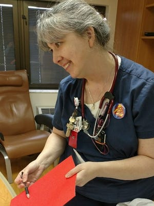 Nurse Christine Brenneman reviews a chart with one of her patients at Community Health Network.