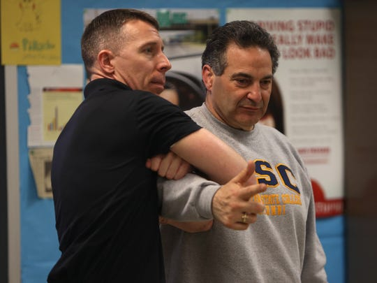 ALICE instructor, Detective Derek Jones of the Georgetown (MA) Police Department wraps up 'bad guy' Lou Sylvester of the North Warren school district showing how to swarm a person wielding a gun as Roxbury police officers, along with about 80 other law enforcement and school officials go through ALICE training, preparing for a school shooter and other scenarios throughout the halls of Roxbury High School. March 29, 2016. Roxbury, N.J.