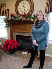 The fireplace behind Sharon Molinaro is decorated with