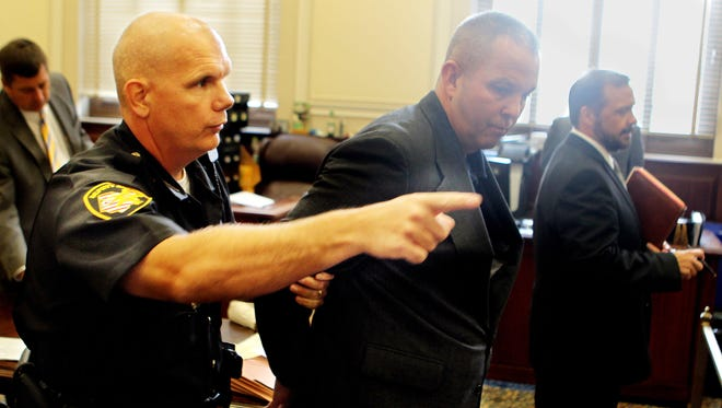 Hamilton County sheriff's Sgt. James Erpelding (right) is directed from the courtroom by a deputy after Erpelding pleaded not guilty to prostitution and procuring charges.  He was released on a no-fee (own recognizance) bond but was taken into custody briefly for processing.