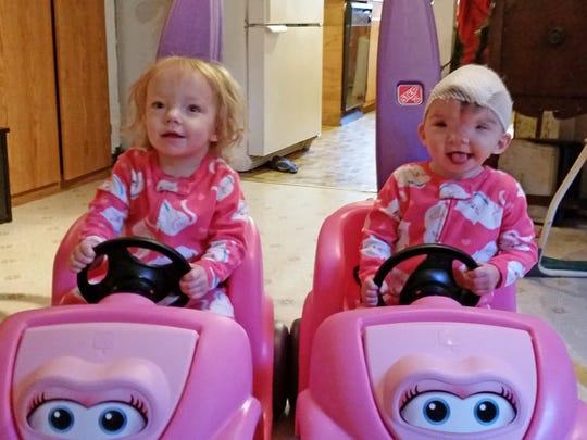 Twins Cora and Violet Pietrok of Stayton play in their matching pink cars.