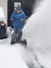 Brigitte Savino, of Southport, blows snow from the