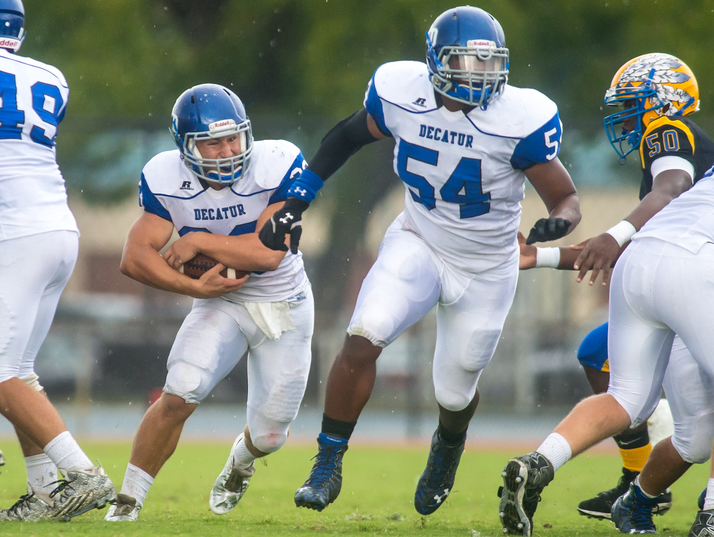 Stephen Decatur left tackle Ernest Shockley (54) clears a hole for running back Dryden Brous (33) against Wicomico High on Saturday afternoon at Wicomico County Stadium.