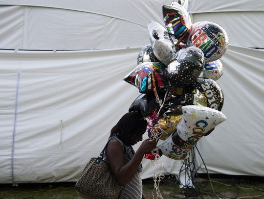 A woman carries balloons to the commencement as Cumberland