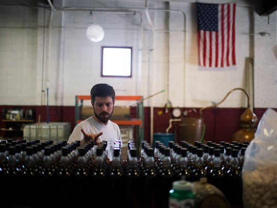 Chief distiller James Yoakum counts bottles of brandy at Cooper River Distillers in Camden in this file photo.