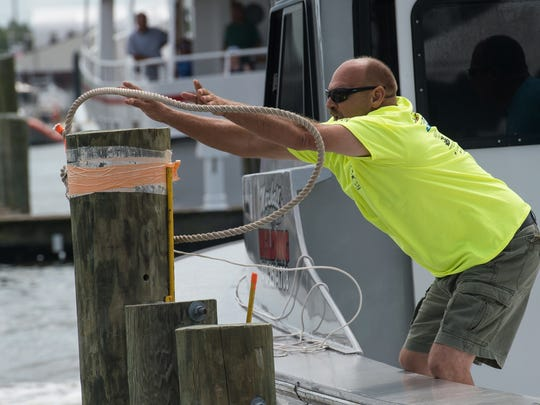 Kevin Marshall, Captain of the Fabricator, tosses a rope onto a post as part of a boat docking competition.
