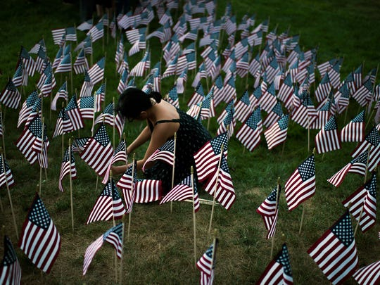 Scout leader Khamh Pham of Turnersville helps plant flags Tuesday, Sept. 6 at McGuinness Funeral Home in Washington Township. Boy and Girl Scouts place the flags in the shape of a heart to honor those killed in the 9/11 attacks.