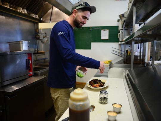 Anthony Leonardi, line cook at Fish on, prepares wings. Thursday, Oct. 27.