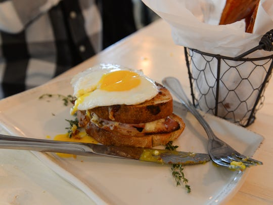 The Croque Madame- A classic ham & gruyere bechamel sandwich on housemate country bread topped with a sunnyside-up egg. Also, with a side of Sriracha bacon candy. Tuesday, Nov. 30, 2016.
