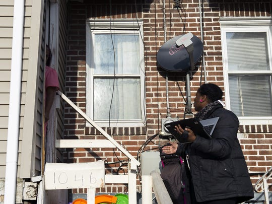 Inspector Toy Humes speaks with a resident n North Camden as she conducts an exterior inspection of the property.