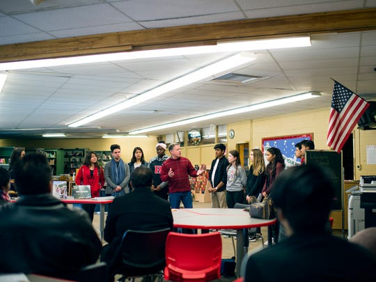 Principal Thomas McCann, center, stands with past and future student travelers Friday, Jan. 6 inside the school's library in Vineland.