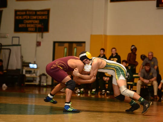 Two wrestlers square off in a wrestling match.