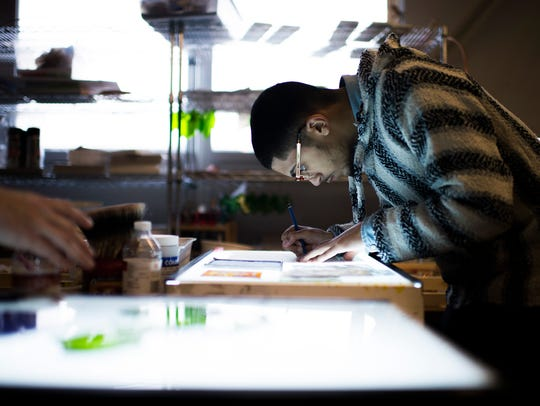 A student works on a sketch for the project Friday,