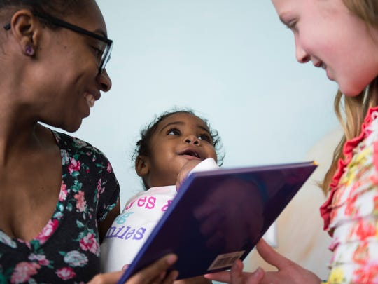 McKenzie Griggs-Ross, 1, looks up at Charlotte Olson, 12, after receiving a new book Tuesday at Children's Regional Hospital at Cooper in Voorhees. Olson collected about 1,300 books and raised $220 as part of a self-initiated service project.