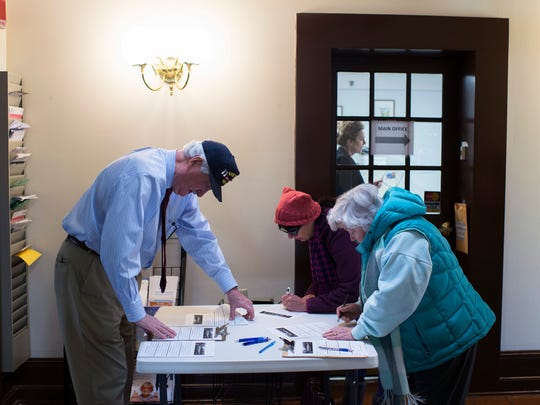 Protesters sign in with help from a staff member (left) inside the office of Congressman Tom MacArthur, R-NJ, Friday in Marlton.