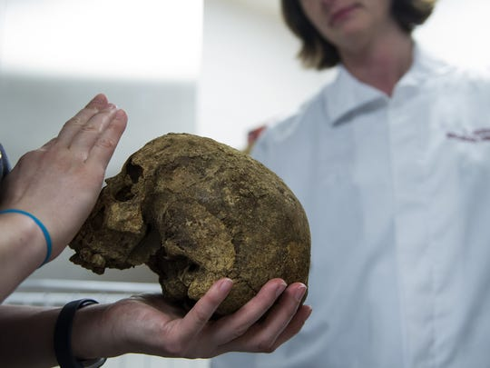 Forensic anthropologist Ani Hatza inspects a female skull dating back to the 18th or 19th century Wednesday, March 22 at Rutgers University in Camden.