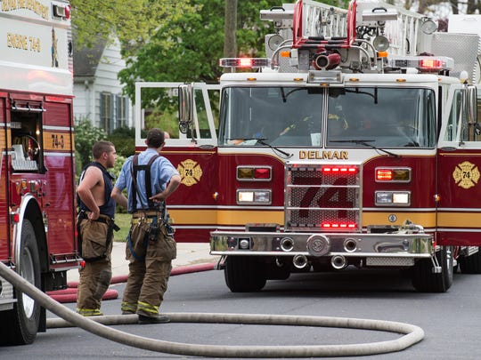Firefighters position outside of a house fire on Walnut