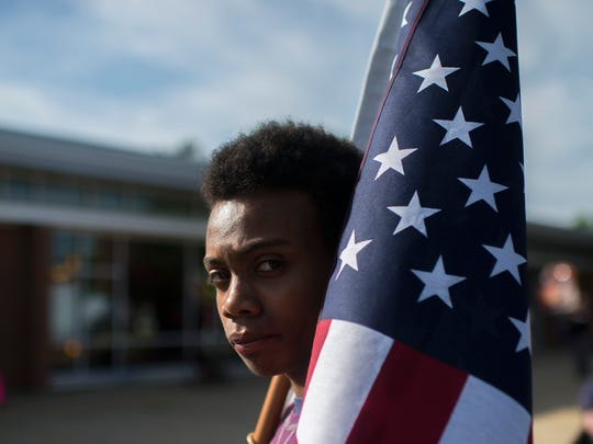 John Larrier of Maplewood stands with an American Flag as protestors gather before a town hall meeting from Congressman Tom MacArthur (R-NJ) in Willingboro.