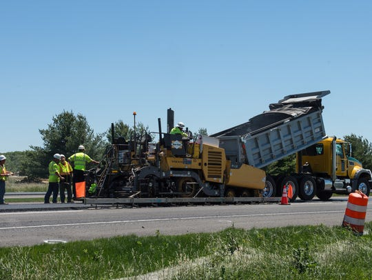 A road construction crew paves a section of Route 13