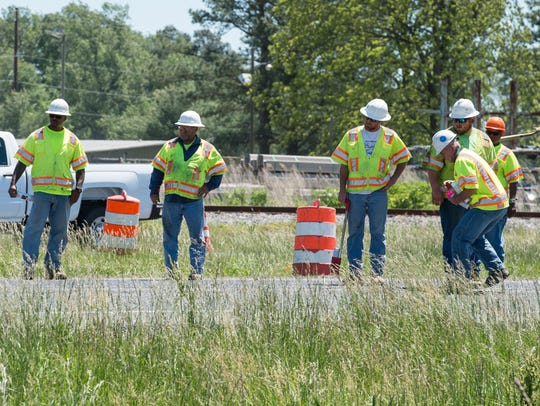 Road crews measure and mark a section of Route 13 near