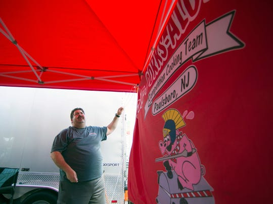 Michael Licciardello of Sir-Porks-Alot-BBQ helps hang their official competition flag Friday, July 7, 2017 in Wildwood.