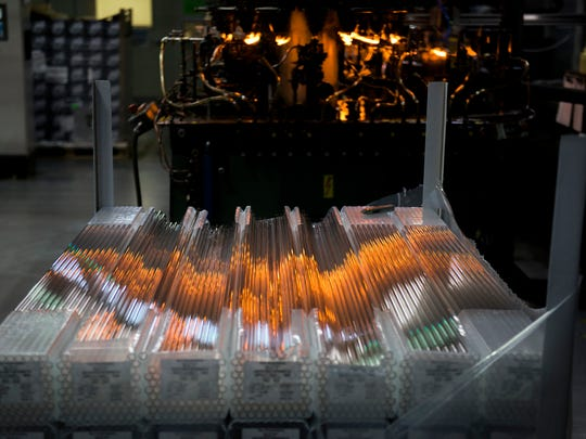 Stacks of vial tubing reflects flames from a machine