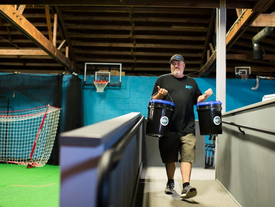 Co-owner Michael Cattell carries buckets of balls into