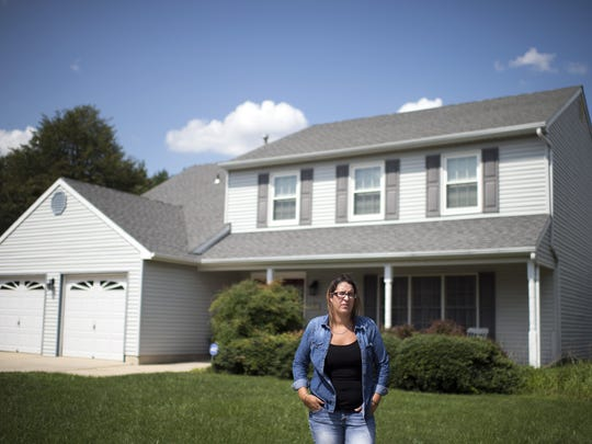 Ashley Miller, 28, poses in front of her grandparents' home in Sewell. Miller is in recovery for pain pills and heroin and is studying to become a certified drug and alcohol counselor.
