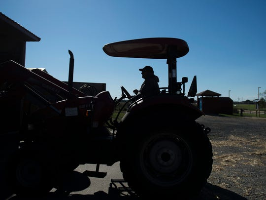 Kenneth Carlisle, 60, loads corn feed for his flock of nearly 300 sheep Tuesday, Oct. 31, 2017 on his farm in Moorestown, New Jersey.