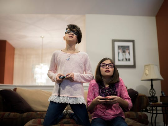 "Maryelena Baldassarre, 11, left, plays video games with her twin sister, Annalisa Baldassarre, at their Sicklerville home. Maryelena was born with a facial deformity, and can identify with the main character in the upcoming movie, ""Wonder."""