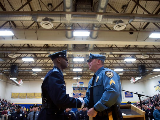 Vineland police officer Maruba Harris, left, receives