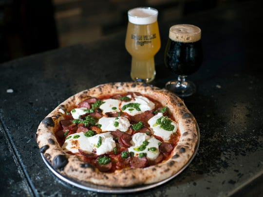 A 'Penelope' pizza is topped with house made pepperoni, fresh house ricotta and basil pesto, paired with a 2nd Street blonde ale (left) and an Oatis oatmeal stout at Urban Village Brewing Company in Philadelphia.