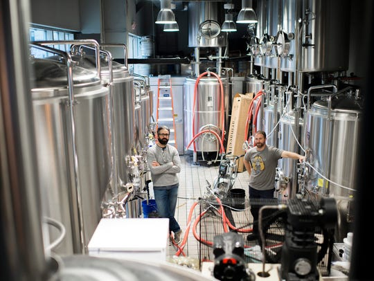 Owners Tom Revelli (left) and Dave Goldman tour the brewery at Urban Village Brewing Company in Philadelphia.