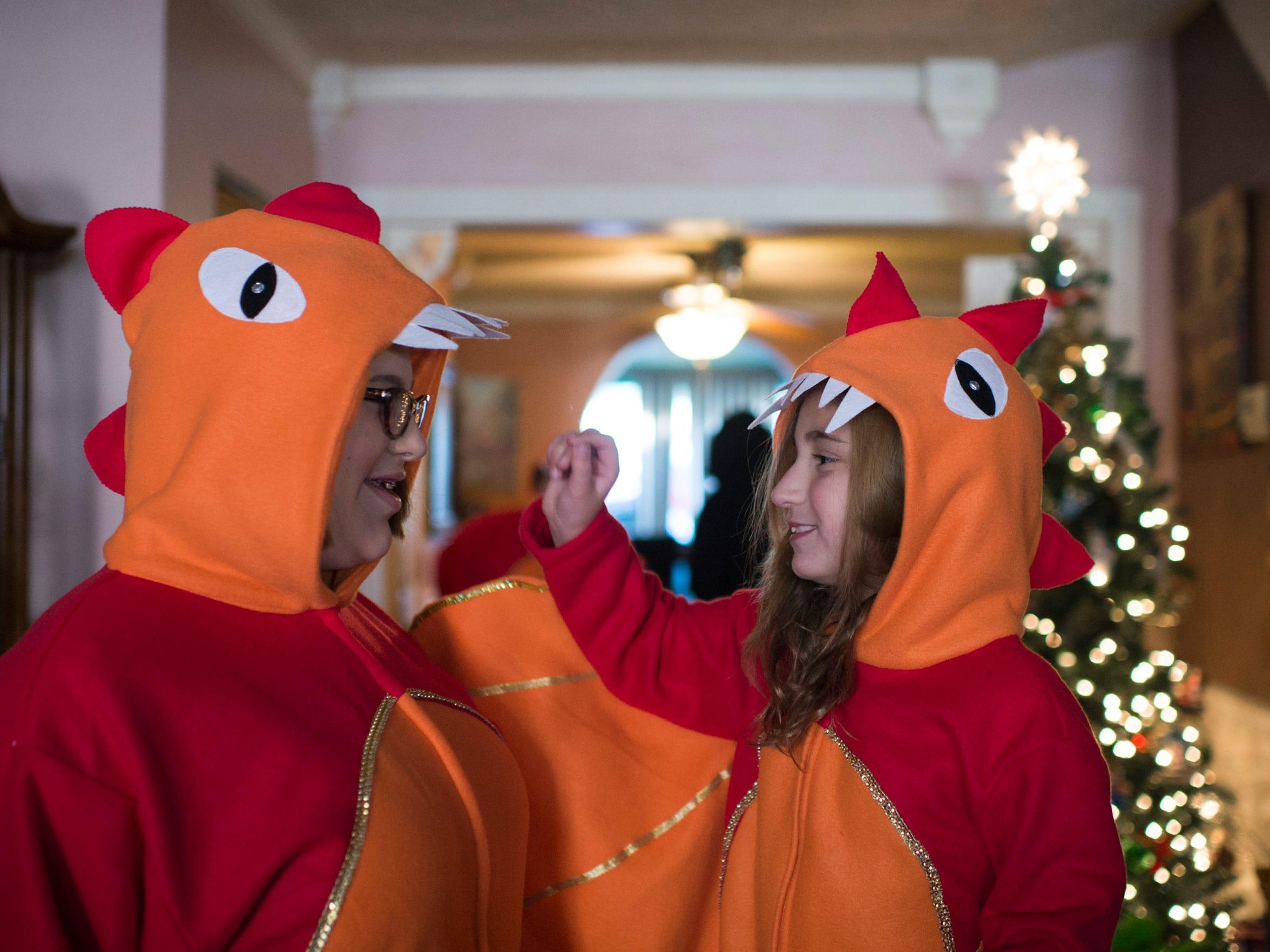 Sophia Stagliano, 8, right, helps Justina Russino, 18, adjust her dragon costume.