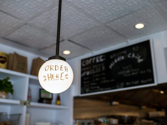 An 'order here' bulb hangs over the front counter at Middle Child in Philadelphia. The deli and diner walks the line between hip and authentic.