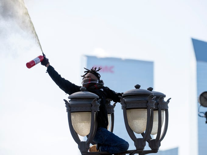 A fan sprays a fire extinguisher atop a light post