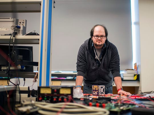 PhD student Russell Trafford, 25, poses with parts of a nano satellite Thursday, Feb. 22, 2018 at Rowan University in Glassboro, N.J. The satellite will be launched into orbit and spend time on the International Space Station with the goal to test new memory technology and how it holds up in space.