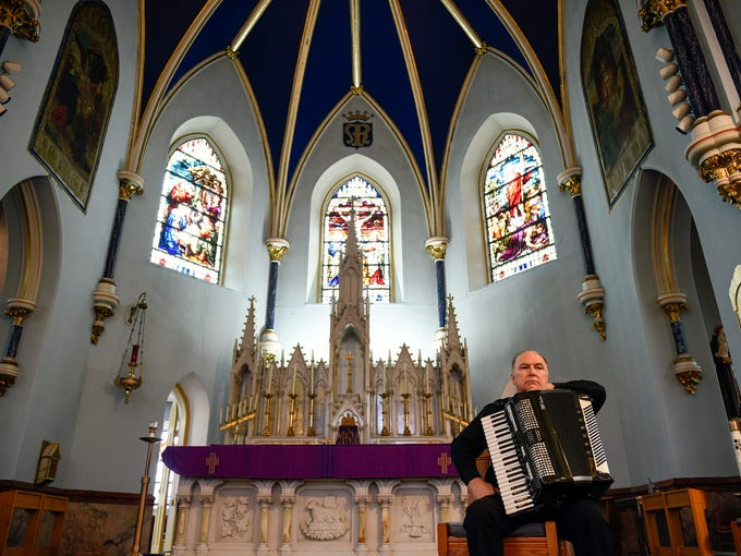 Monsignor William Hodge sits with his accordion after