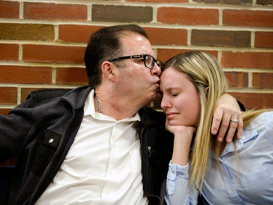 Steve McDonald kisses his 19-year-old daughter, Devon McDonald, while discussing the loss of her younger sister, 15-year-old Madison McDonald. The Marlton family attended a pretrial detention hearing Wednesday for Austin F. Cooper, 21, a Willingboro man charged with strict liability for the teen's overdose death.