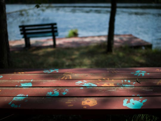 Handprints are seen on a picnic bench overlooking the
