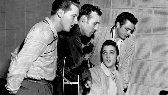 The only thing predictable about Elvis is that he's unpredictable. On Tuesday, December 4, 1956, Carl Perkins (second from left) was cutting some new records at Sam Phillips' Sun Record studio on Union at Marshall. Elvis Presley dropped in. So did Johnny Cash (right). Jerry Lee Lewis (left) was already there. Elvis headed for the piano, and an old-fashioned barrelhouse session with barbershop harmony resulted. Accompanying Elvis was his house guest (not pictured) Marilyn Evans, 19, a dancer at the New Frontier in Las Vegas.
