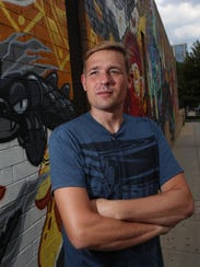 Chris Barth poses for a portrait next to the building
