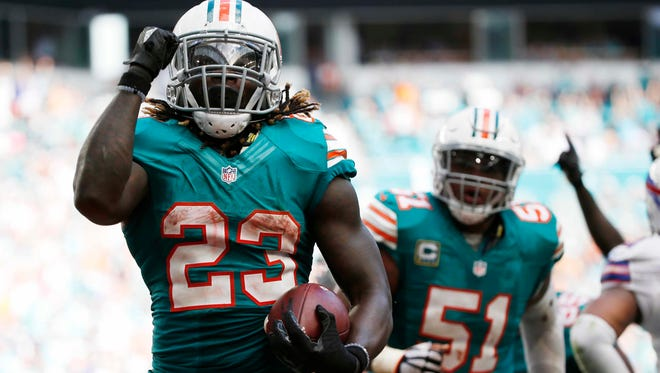 Miami Dolphins running back Jay Ajayi (23) celebrates a touchdown during the second half of an NFL football game against the Buffalo Bills, Sunday, Oct. 23, 2016, in Miami Gardens, Fla. To the right is Miami Dolphins center Mike Pouncey (51).